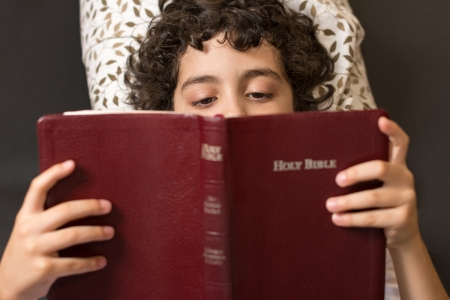 Young Hispanic child reading and studing the Holy Bible at home  Daily devotional and reverence of a boy  Taking a break and meditating on the word of God  Love of a child for his Creator in Heaven Фото со стока