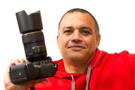 profile picture: Hispanic photographer holding a camera on his right hand and wearing a red sweater  Man slightly smiling  Professional profile picture of a photographer