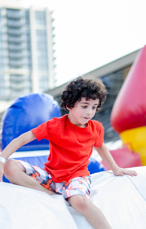 Young boy playing and having fun in an inflatable playground set in a city s neighbourhood  Imagens