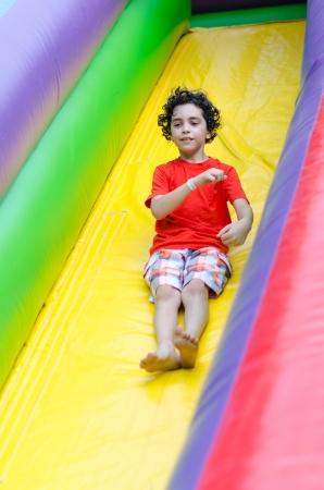 若い男の子遊んで楽しんで、膨脹可能な遊び場で市 s 地区設定