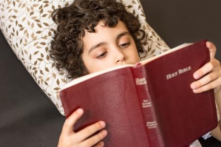 historias de la biblia: Niño hispano joven leyendo y estudiando la Biblia en casa Devocional diario y la reverencia de un niño tomando un descanso y meditación de la Palabra de Dios El amor de un niño por su creador en el cielo Foto de archivo