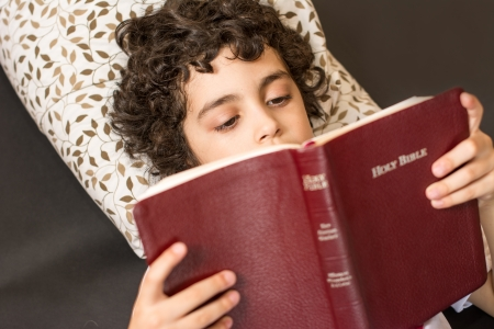 Young Hispanic child reading and studying the Holy Bible at home  Daily devotional and reverence of a boy  Taking a break and meditating on the word of God  Love of a child for his Creator in Heaven