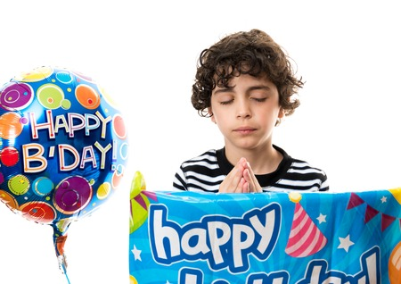 child praying: Hispanic child praying before his birthday party  He wants it to be a success  Religious image of a boy on his birthday day Stock Photo