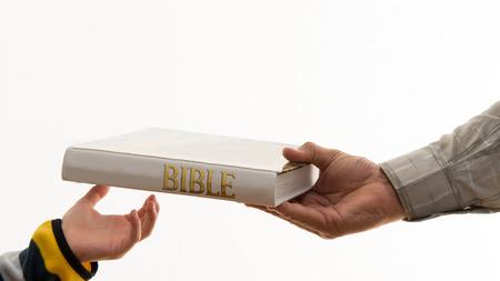 私たちの信念を引き渡します。古い mand 新世代に聖書を引き渡します。古い教育を受けた若い子供の手。キリスト教を引き渡す