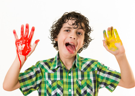 smeared: Happy Hispanic child gesturing at the camera with his two hands painted. Watercolor mess at home. Not a funny way to have fun. Kid enjoying his free time playing with watercolor paint. Stock Photo