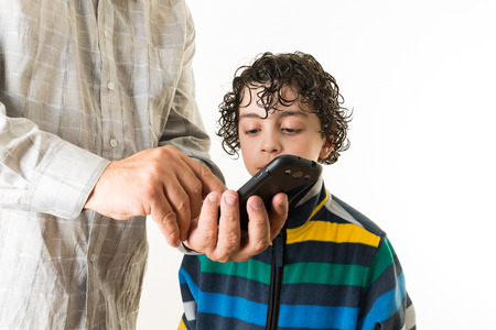 Teaching the new generation about technology. Father shows his son the different features of a smart phone. Education in gadgets over a white background photo