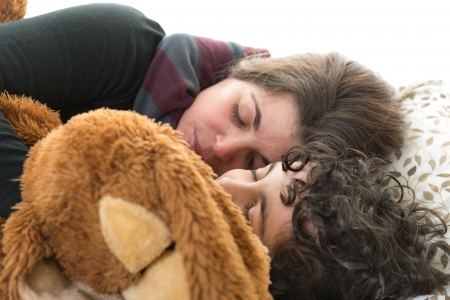 Single mother sleeping with her son and a teddy bear. Candid picture of a small family. Normal life at home. Hispanic family over white background. Isolated people sleeping. photo