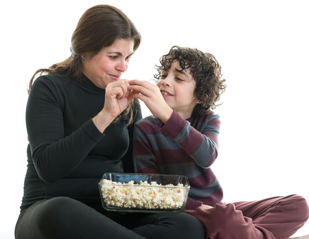 Hispanic single mother sharing popcorn with her eight years old son. Latin family enjoying the simplicity of life. White background. People isolated and in action photo
