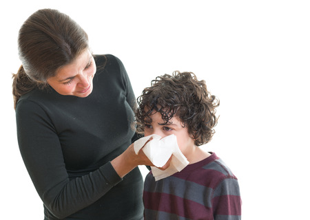 Single mother helping her son to blow his nose. Scene over white background. Hispanic family helping each other during sickness photo