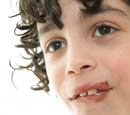 smeared: Close up of a childs face. Mouth smeared of chocolate ice cream. Large permanent teeth. Stock Photo