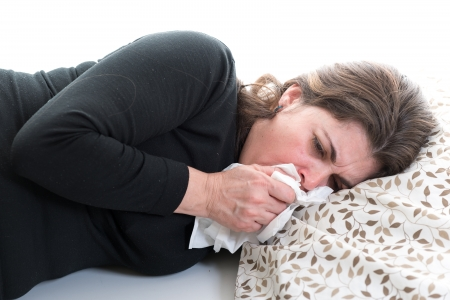 Hispanic woman on bed with a virus. Middle aged woman blowing her nose and suffering form a cold. Sick lady in bed