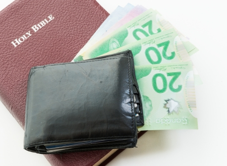 brethren: Holy Bible with money on top. Representation of the Christian offering. Giving money to the church. Providing for the brothers in Christ. Supplying for the brethren in need. Stock Photo