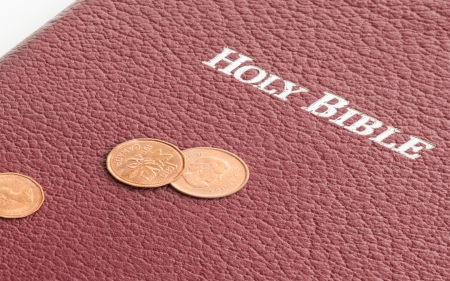 Holy Bible with money on top. Representation of the Christian offering. Giving money to the church. Providing for the brothers in Christ. Supplying for the brethren in need. Stock Photo