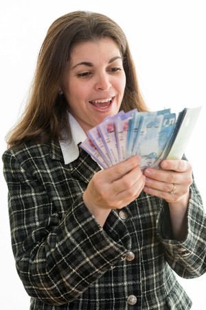 Happy Hispanic woman counting Canadian dollars. Successful business woman in Canadas multicultural society. White background. Enjoying the fact of having money