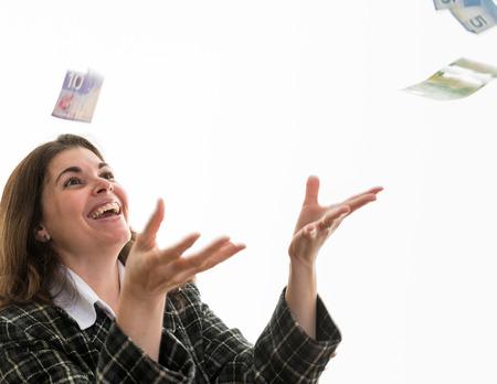 dare soldi: Ispanico, donna, buttare i soldi per l'aria. Felice donna godendo di un premio in denaro. Allegro donna godendo il suo avere soldi. Celebrare un business di successo Archivio Fotografico