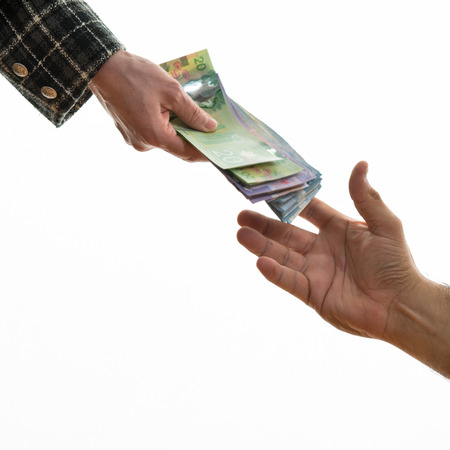 Woman hand handing Canadian money to a male hand. Over white background. Doing business between women and men.