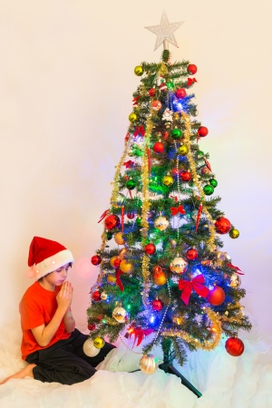 kneeled: Boy child praying in front of a Christmas tree. Hispanic kid asking Santa for his Christmas present. Child kneeled in humility asking God for his Holiday gift Stock Photo
