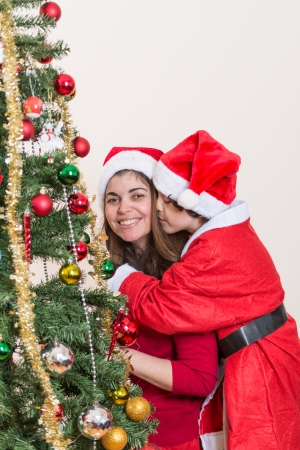 Single mother and son having fun while setting up the beautiful Christmas tree. Boy kissing mother around a Christmas tree. Small family fun photo