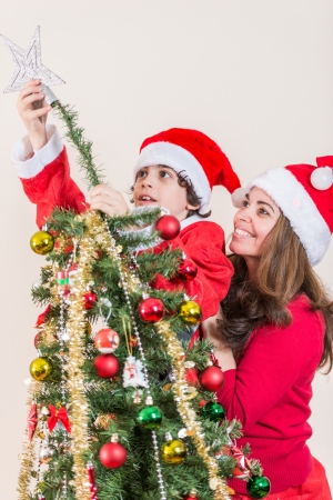 Beautiful Christmas scene at home  Single mother and son setting up the Christmas tree photo
