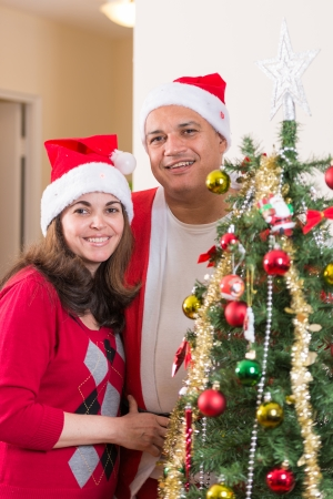 Hispanic couple portrait close to a beautiful Christmas tree they put together