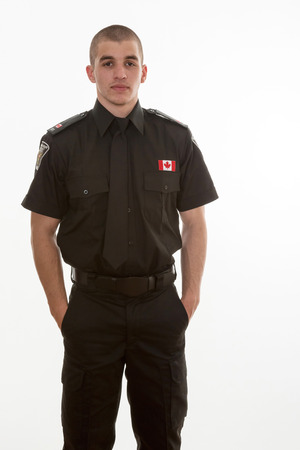 Police student in uniform standing over a white background. Canadian teenager in college studing to serve and protect