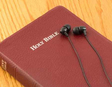 Holy Bible with a resting pair of earbuds over it  The word of God through hearing  Believing through hearing  Religion for the blind photo