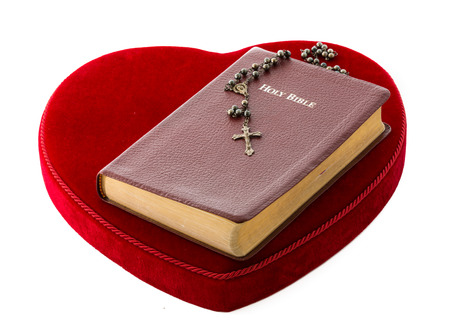 eternal life: Bible over a red heart  Love for the word of God and the eternal life  Protestan cross with two rings of married people  Resilience of a marriage when tied to the faith, love of God and Christ Stock Photo