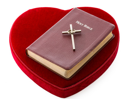 Bible over a red heart  Love for the word of God and the eternal life  Protestan cross with two rings of married people  Resilience of a marriage when tied to the faith, love of God and Christ Imagens