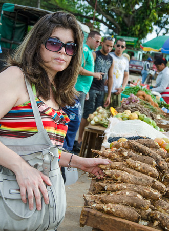 SANTA CLARA,CUBA-JANUARY 9,2013: Woman buying cassava at a newly open private farmers market as the government introduces changes to its economy