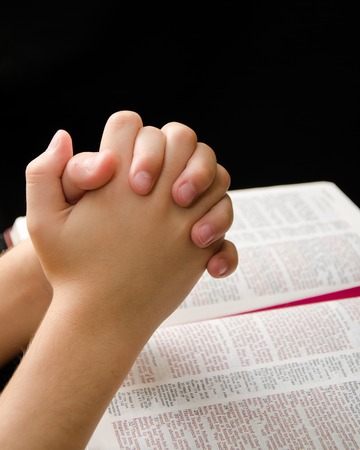Child praying with devotion over an open Bible Stock Photo