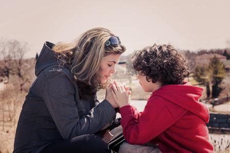 単一の母親と彼女の息子の祈りの屋外を持っています。Instagramesque 効果が付いている都市のために祈って 写真素材