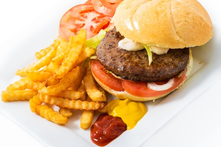 Beef hamburguer in white bread served with french fries,lettuce,tomato,onions,french fries,ketchup,mayonnaise, and mustard.