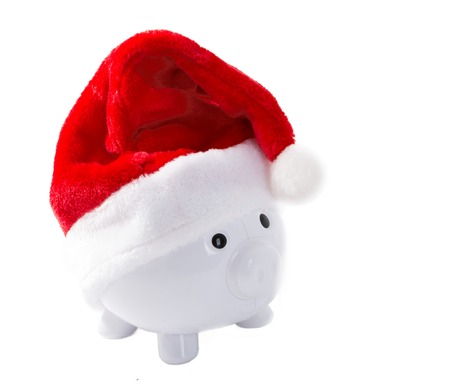 destined: White piggy bank with a Christmas hat and destined for paying Christmas expenses Stock Photo