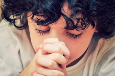 christian youth: Hispanic child devotedly praying to his Creator in Heaven. Christian worship and relationship. Image has been filtered for effect Stock Photo