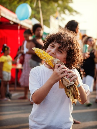 効果と気分のためトロント画像の通り祭りのトウモロコシの穂軸でトウモロコシを食べるヒスパニック系の少年がフィルター処理されました。
