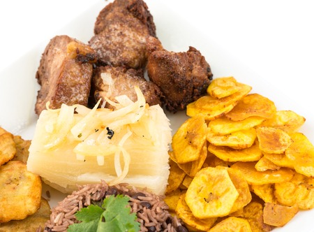 Deep fried pork, yukka or cassava plus congri rice all with salty green banana fries  Typical Cuban Meal photo