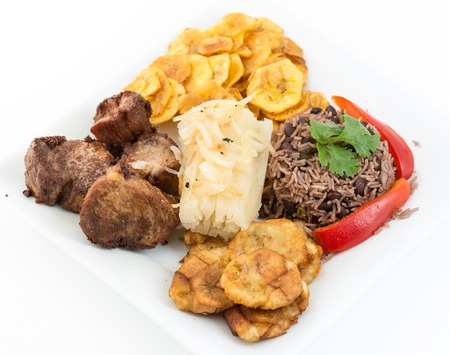 Deep fried pork, yukka or cassava plus congri rice all with salty green banana fries  Typical Cuban Meal photo