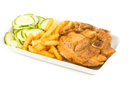 Pork sirloin chop cooked using the Cuban cuisine style and served with cucumber salad and french fries photo