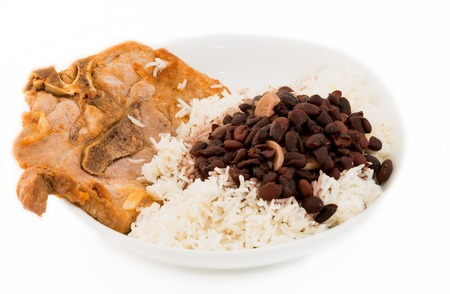 Pork sirloin chop cooked using the Cuban cuisine style and served with the traditional rice and black beans soup. photo