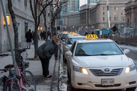 catching taxi: TORONTO,CANADA-MARCH 13,2014: Downtown Toronto Images. Downtown Toronto is the primary central business district in Canada an it is located entirely within the former municipality of Old Toronto