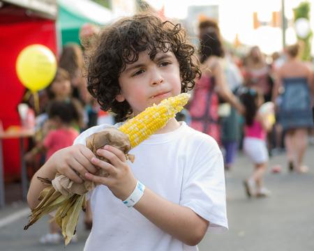 少年は、街のお祭りでコブにトウモロコシを食べる