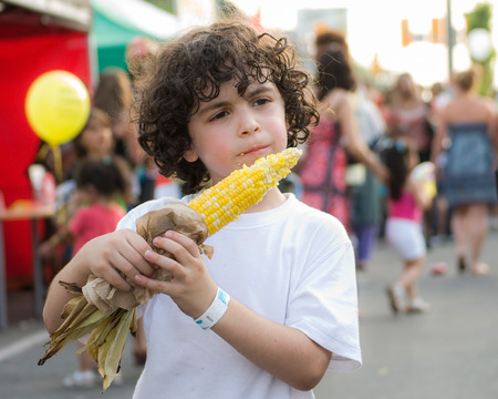 A boy eats corn on the cob in a citys festival