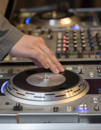 Hand of a DJ rotating his equipment to produce effects. DJ professional equipment operated by a skillful Disc Jockey