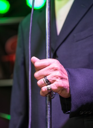 live performance: Salsa singer detail while holding the microphone in a live performance Stock Photo