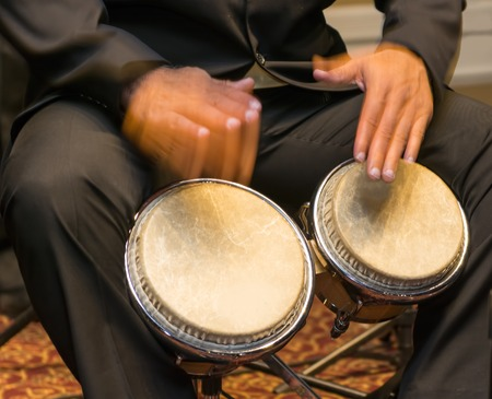 american music: Salsa musician playing the bongos, a percussion instrument traditional for the Caribbean and Latin American music