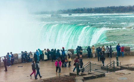 NIAGARA FALLS, CANADA-APRIL 18, 2014: Tourists walking along the Niagara River and enjoying the beautiful view of the Niagara Falls in the Canadian side one of the major attractions in the country.