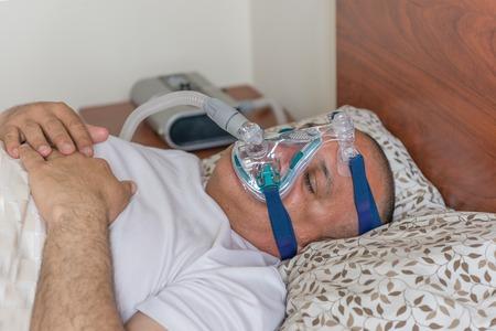 apnea: L'uomo indossa una maschera per il trattamento di apnea del sonno Lievemente uomo obeso che soffrono di apnea del sonno e avendo un trattamento con CPAP
