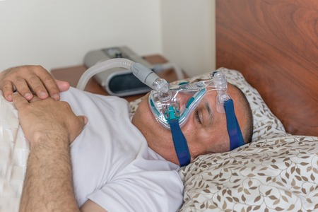 Man wearing a mask for treating sleep apnea  Mildly obese man suffering from sleep apnea and having a CPAP treatment Stock Photo