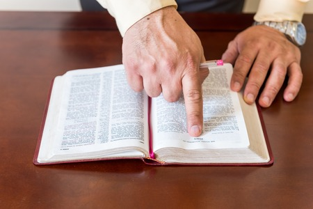Pastor or man of God reading and teaching the Bible to others and to himself in a small circle or house environment photo