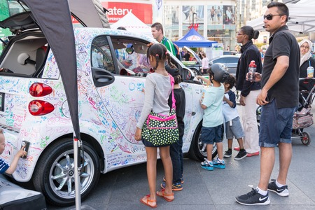TORONTO,CANADA-MAY 24, 2014  Smart cars marketing its electric cars to children in Dundas Square  Smart Automobile is a division of Daimler AG that designs, manufactures and markets microcars
